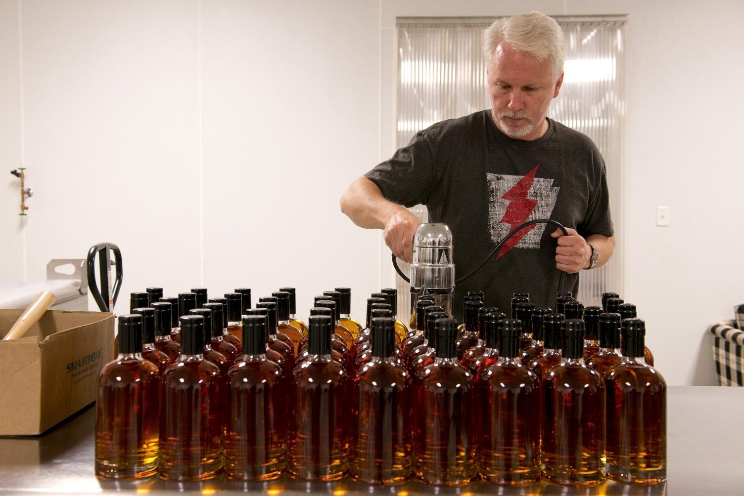 man filling liquor bottles in a distillery