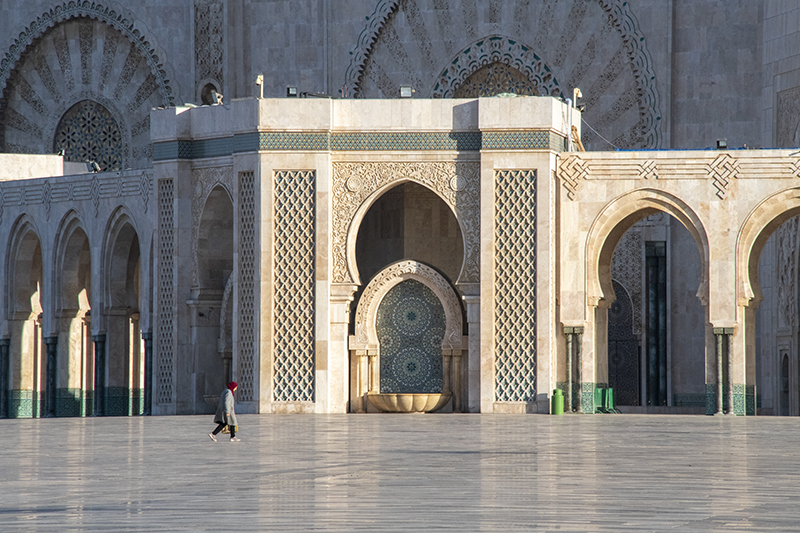 woman walking around a large mosque in Casablanca, one of the things to do in Morocco