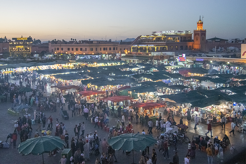 crowds of people in a large public square in Marrakesh, one of the places to visit in Morocco