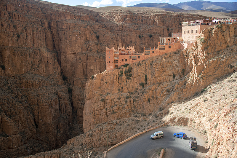 cars passing a hotel on a rock outcrop, a place to visit in Morocco