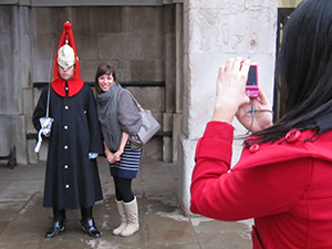 tourists taking photo of soldier at attention