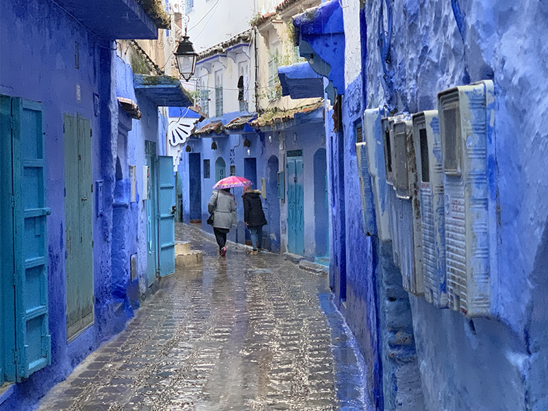 people walking past blue buildings in Chefchaouen, one of the things to do in Morocca