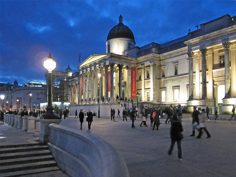 people on an evening walk in London passing a museum