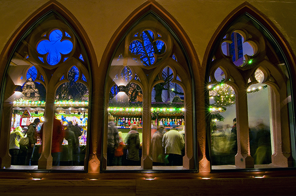 a view of a German Christmas market through gothic windws