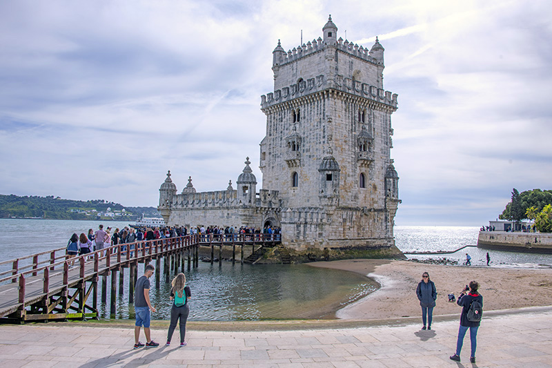 people looking at an old tower, one of the things to do in Lisbon