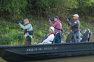 people in a skiff photographing wildlife