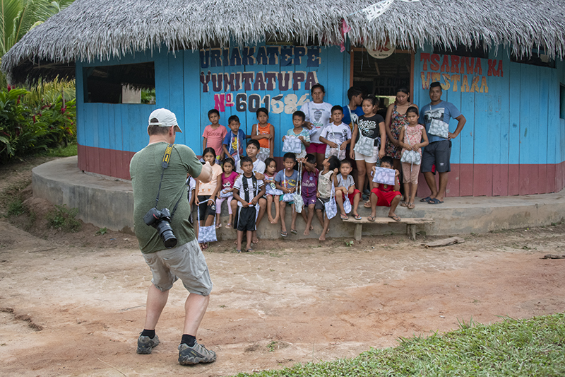 a photograher with children while on an Amazon River cruise in Peru