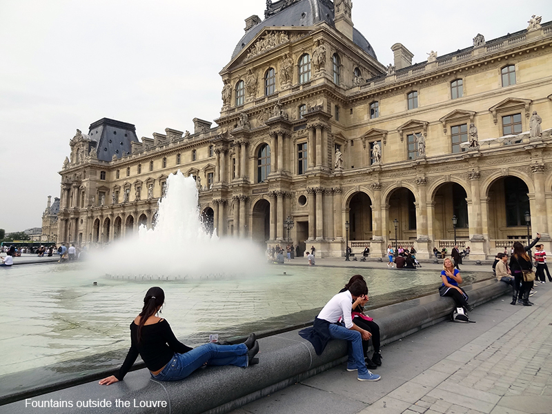 people sitting by a fountain in photos of Paris