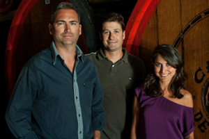 3 people standing by large wine barrels