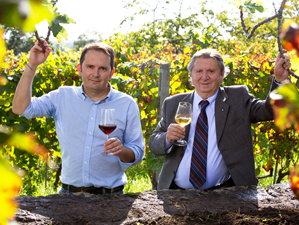 2 men in a vineyard have a glass of wine