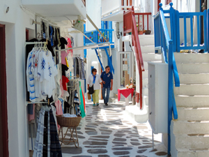 a couple walking past Boutiques in Mykonos Town