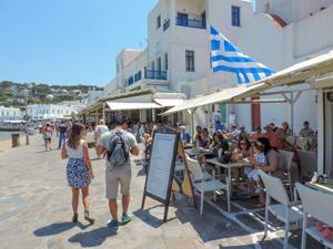a large Greek flag flying over a restaurant