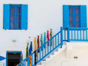 blue shutters and stairs with colorful scarves on a wall in Mykonos Town