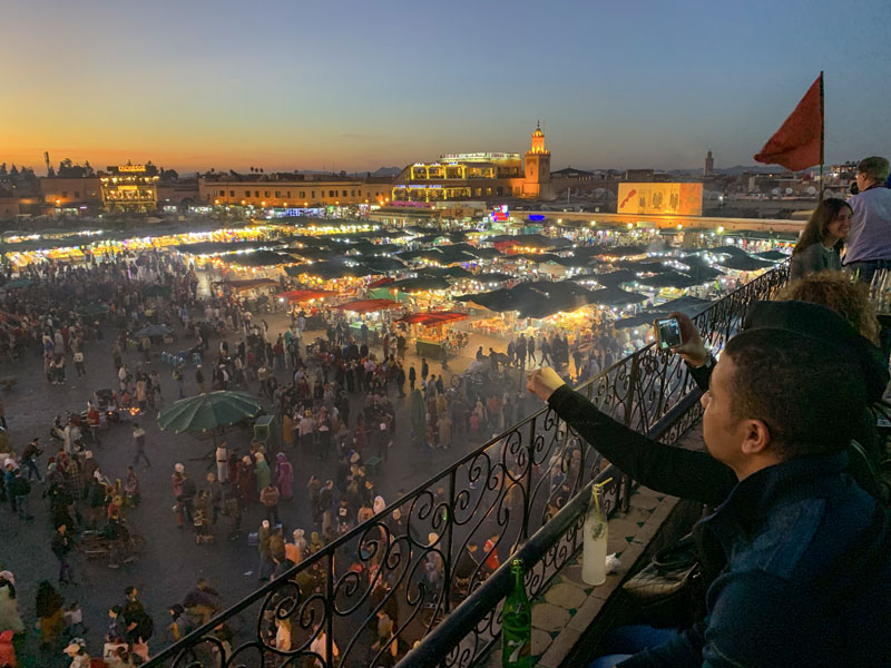 people enjoying the evening at the Jemaa-el-Fna, one of the things to do in Marrakesh