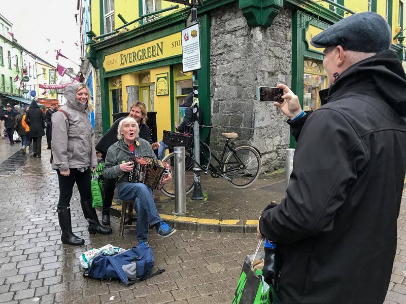 a street musician with 2 women on Ireland's west coast