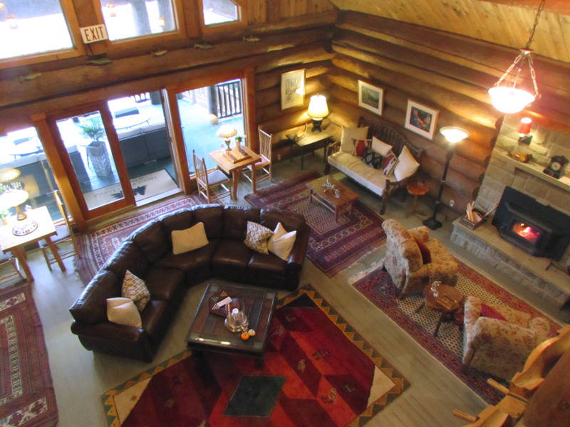 a great room made of logs with chairs and sofas by a fireplace in the Trout Point Lodge
