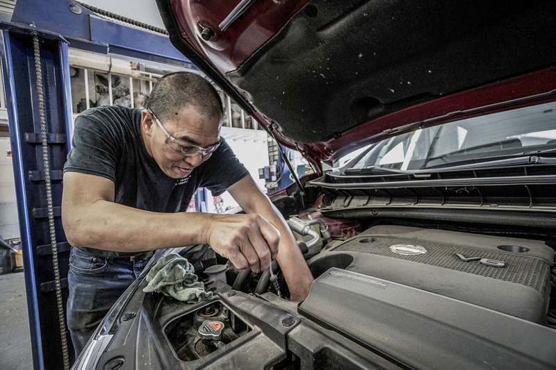 mechanic servicing a car for a best road trip
