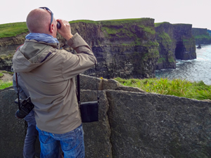 man looking at tall cliffs on Ireland's west coast