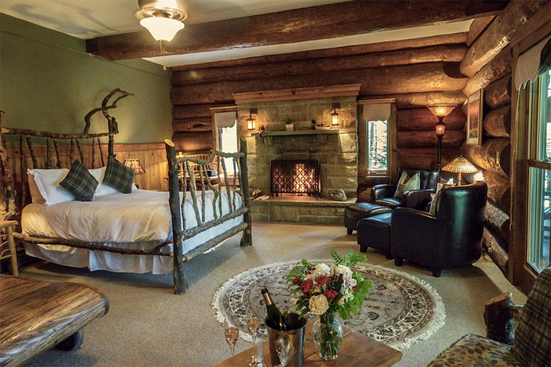 A large bedroom with walls of logs at the Trout Point Lodge