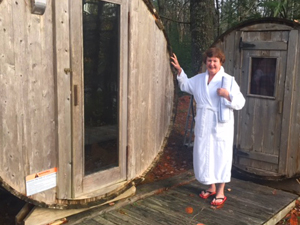 a woman in a white robe standing by a round outside sauna at the Trout Point Lodge