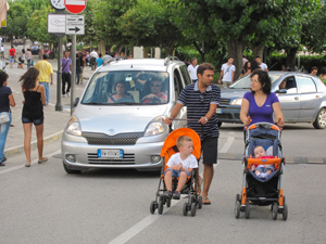 people in the street with baby carriages