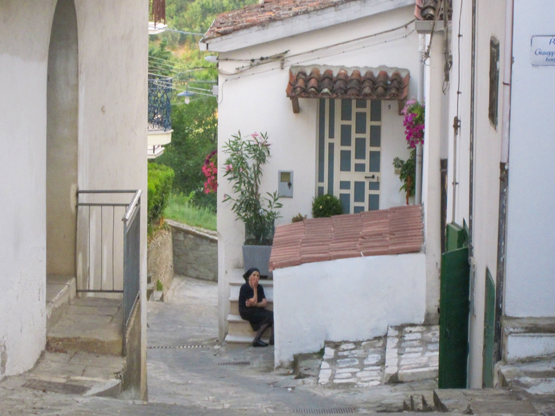A woman sitting on steps on a small street in Accettura