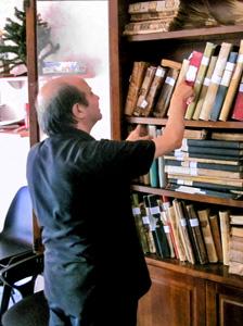 a priest at a bookcase