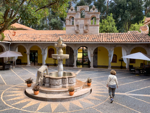 woman walking by an old fountain seen in Cusco and the Sacred Valley in Peru