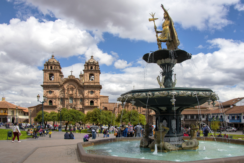 A tsatue of an Inca and a cathedral seen in Cusco and the Sacred Valley in Peru