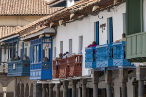 people on wooden balconies on buildings seen in Cusco and the Sacred Valley in Peru