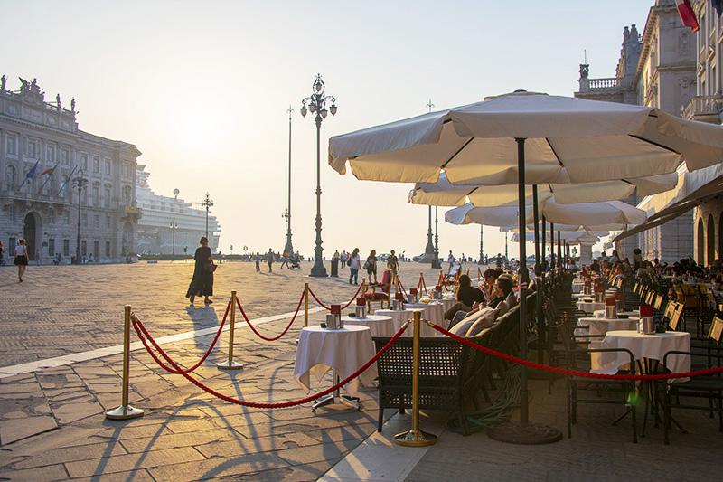 people at a cafe near a cruise ship in Friuli Venezia Giulia