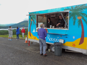 people by a roadside food truck