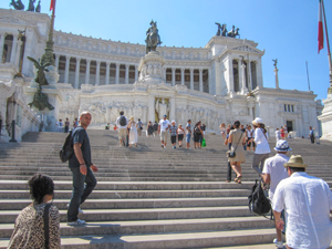 people on the steps of a large monument see on walks in Rome