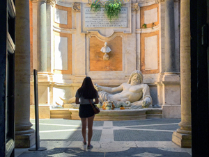 a woman looking at a large statue see on walks in Rome