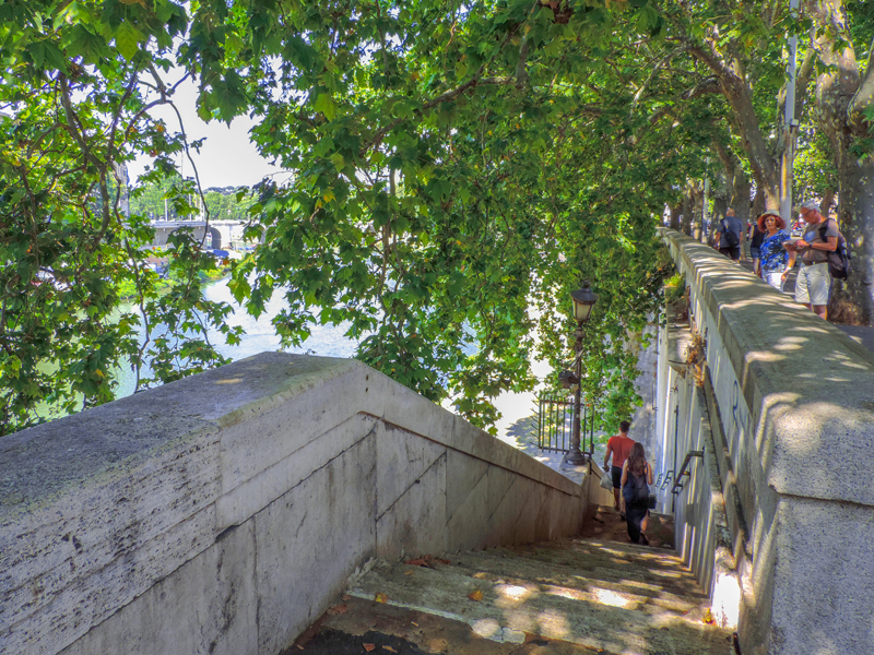 people walking down  stair alongside a river