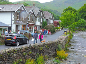 people walking along a brook in a village - one of the attractions of the Lake District