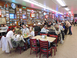 people at tables in one of the delis in New York City
