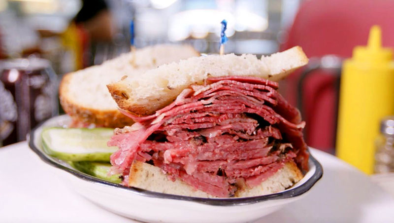 a pastrami sandwich on a plate in one of the delis in New York City
