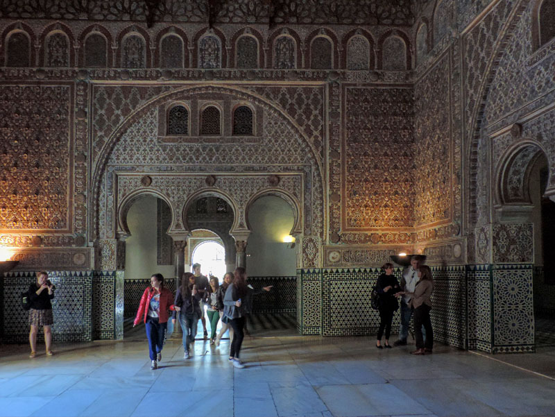 people touring a magnificent Moorish palace,  one of the things to do in Seville