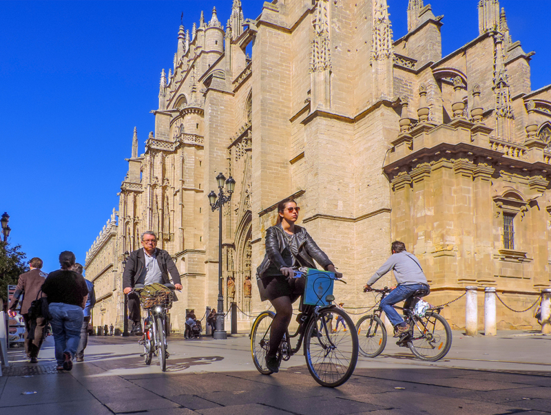 people on bikes near a cathedral, one of the things to do in Seville
