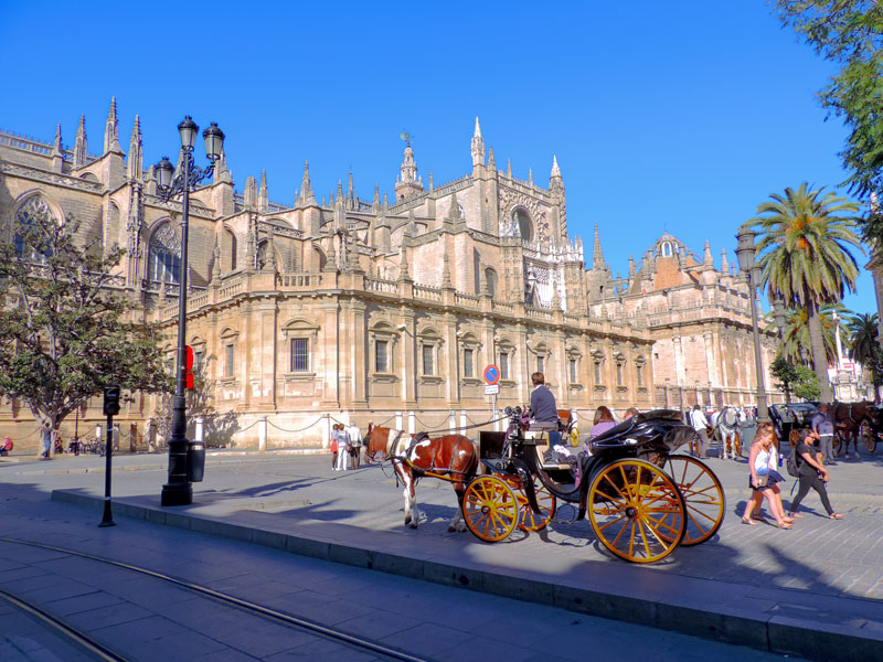 people in a horse-drawn carriage near an ornate building,  one of the things to do in Seville