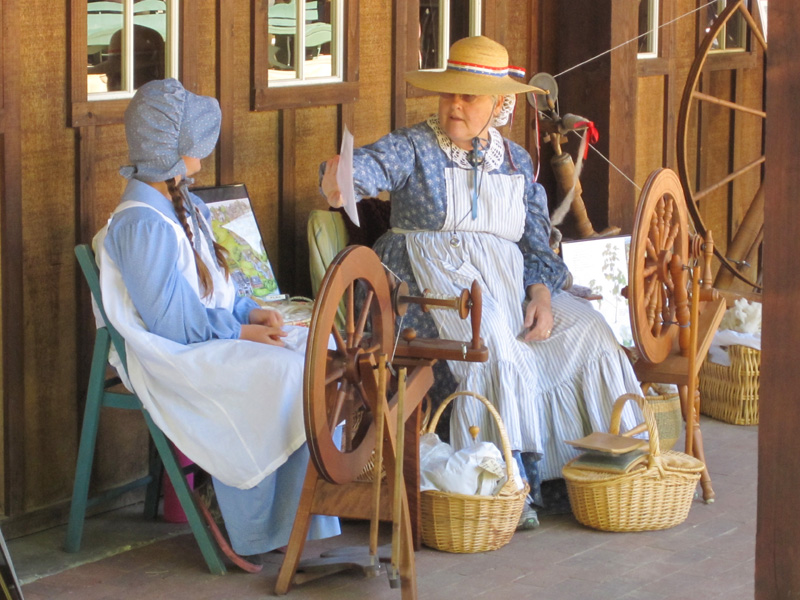 Two women at a spinning wheel at a Civil War reenactments