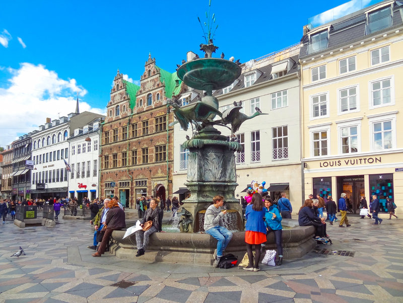 people sitting around an ornate fountain seen during one day in Copenhagen