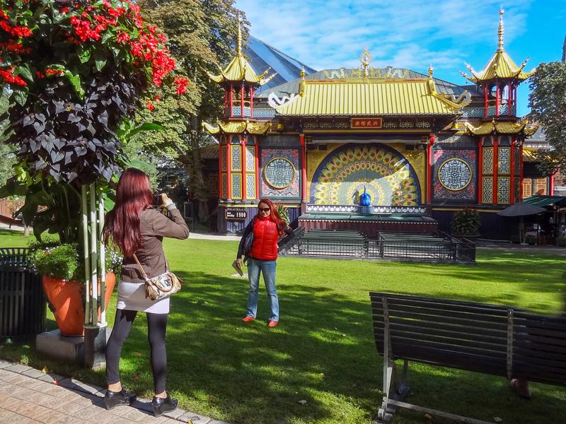 A young woman taking a photo in Tivoli Gardens
