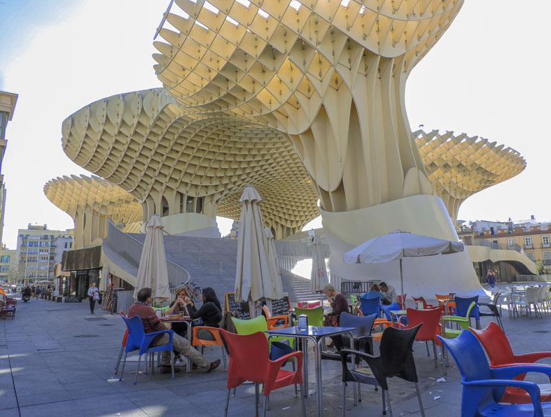 people sitting at tables beneath a large ornate parasol
