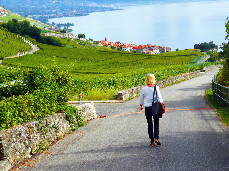 a woman walking down a rod through vineyards in Montreux Switzerland