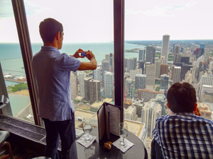 man taking a photo of a city from a tall building