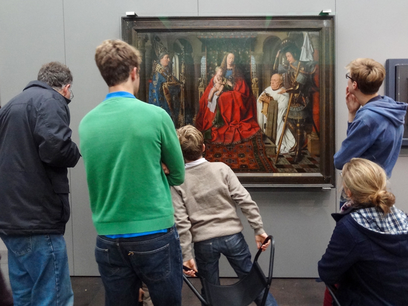 people looking at a painting in one of the places to visit in Belgium