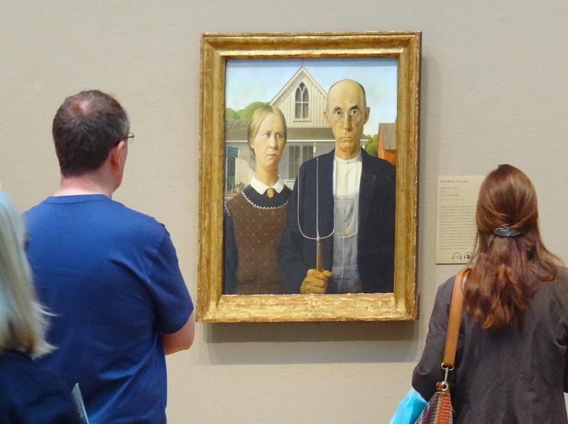 a couple looking at a painting in a museum