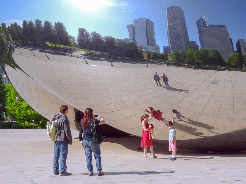 a family by a huge mirror sculpture, one of the things to do in Chicago